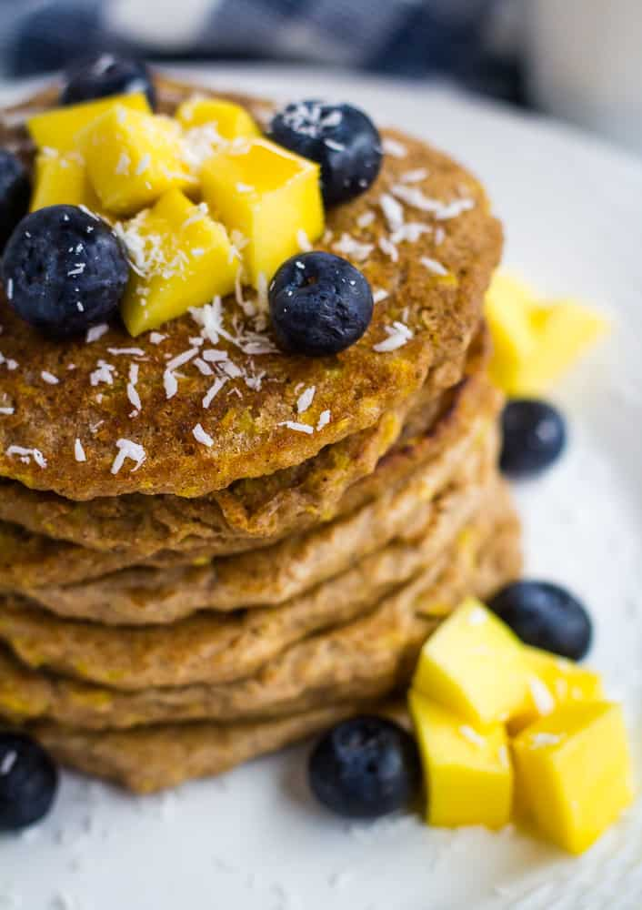 overhead of pancakes topped with coconut, blueberries, and mango