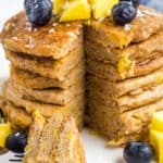 stack of mango pancakes topped with blueberries and mango