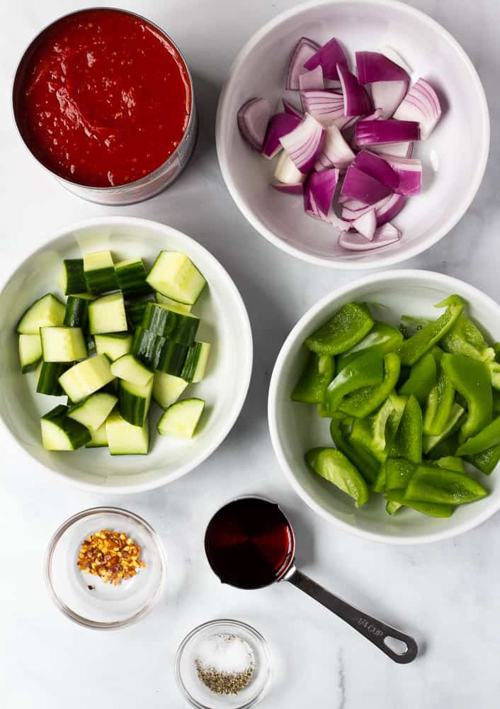 tomatoes, onion, cucumber, green pepper, and spices in white bowls