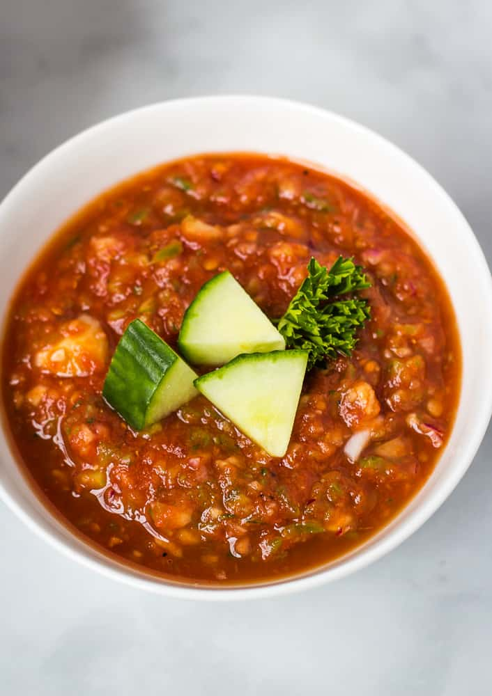 overhead of gazpacho topped with cucumber