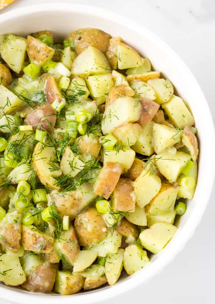 overhead of vegan potato salad topped with dill and scallions