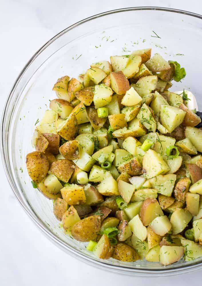 vegan potato salad with fresh herbs in glass bowl