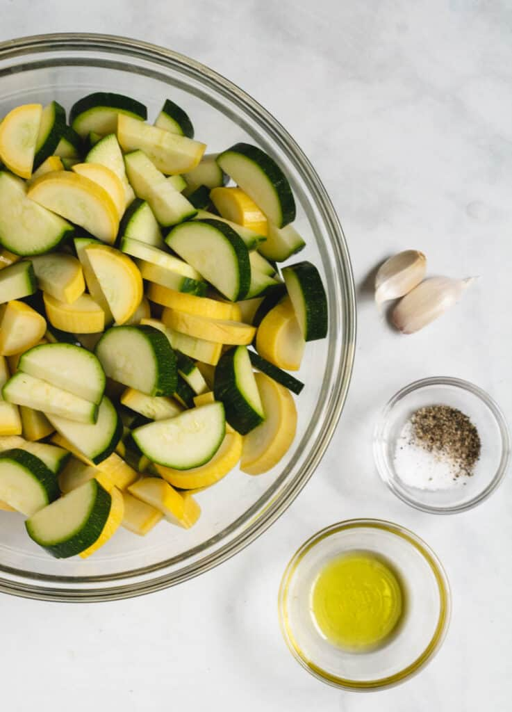 cut zucchini, yellow squash in large bowl with garlic, olive oil and salt and pepper