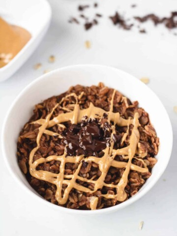bowl of brownie oatmeal topped with peanut butter and chocolate shavings