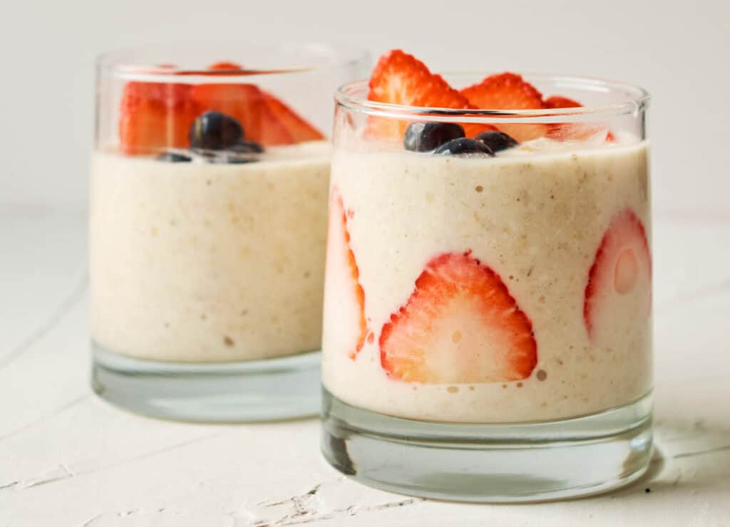 two cups of overnight oats topped with berries