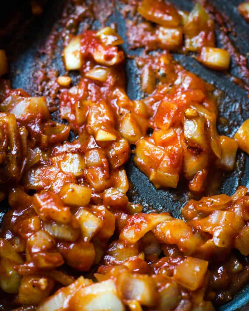 onions in tomato paste in pan