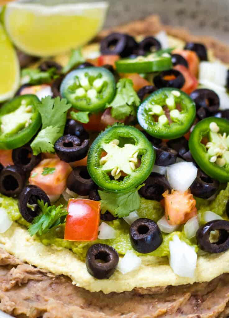 close up of layered bean dip with olives and jalapenos