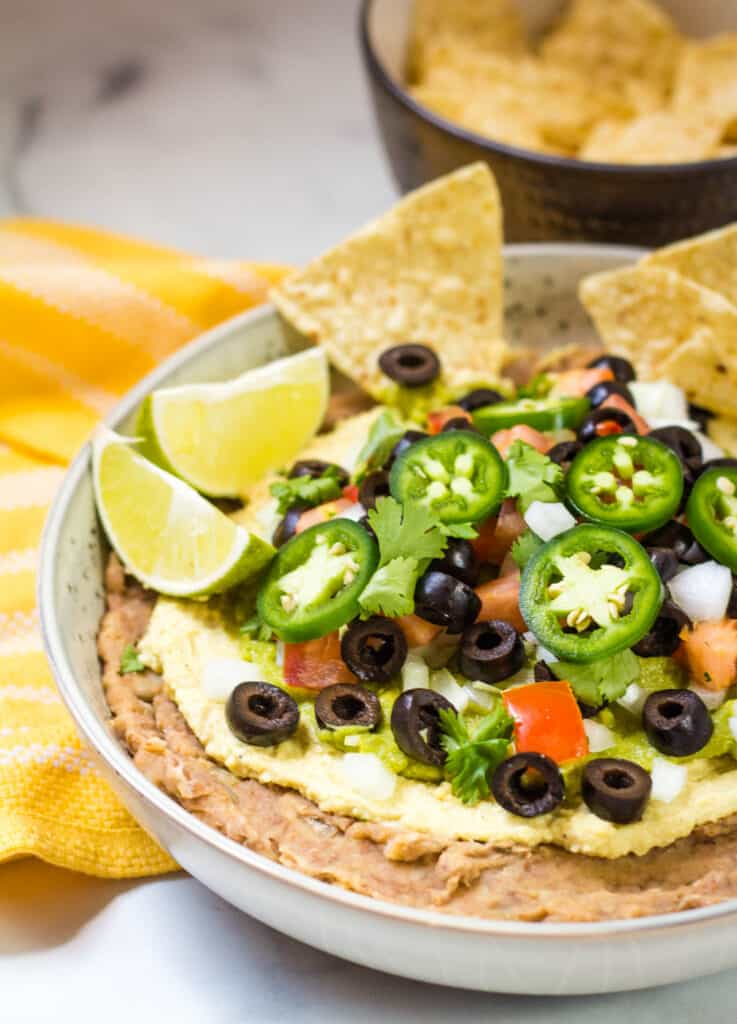 bowl of 7 layer dip with chips and lime