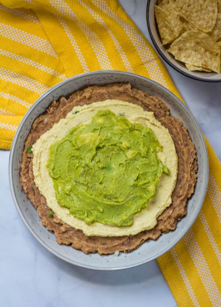 refried beans in grat bowl topped with cheese sauce and avocado spread