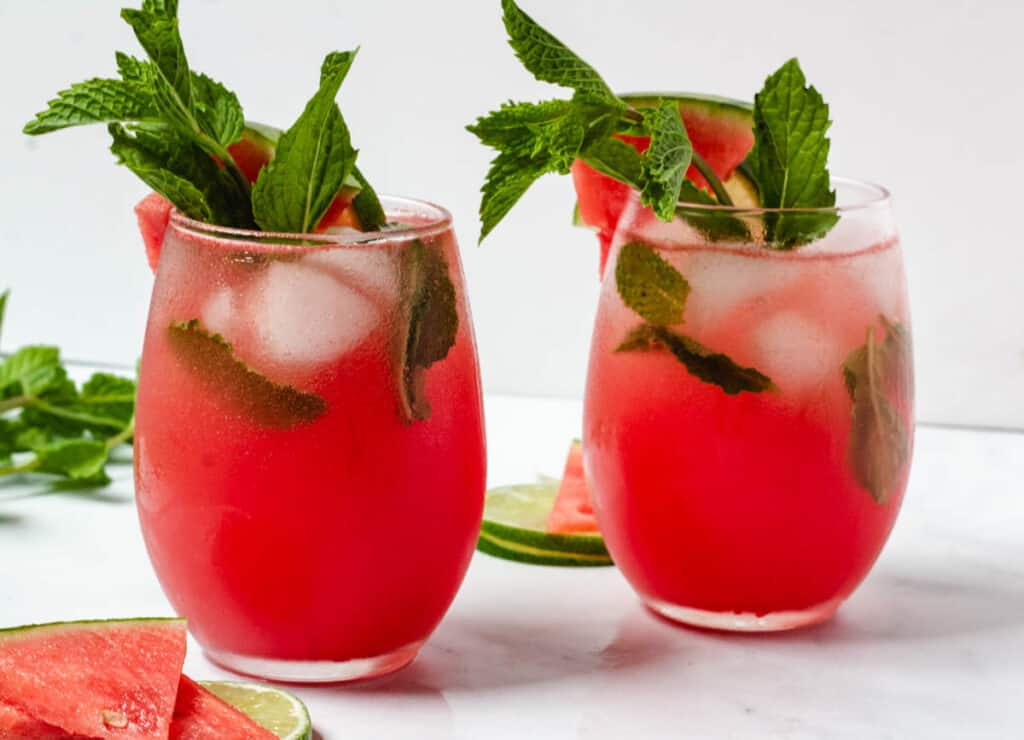 two glasses of watermlon moctails garnished with mint