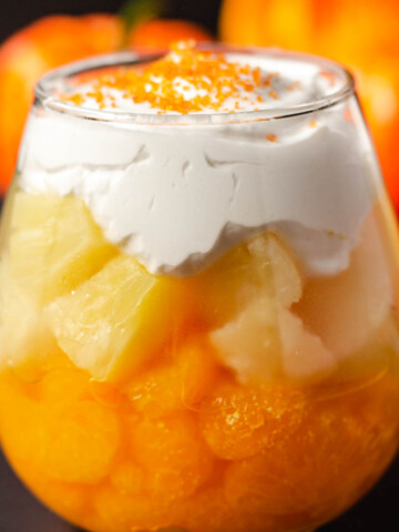 candy corn fruit parfait with mandarin oranges, pineapple, and whipped cream