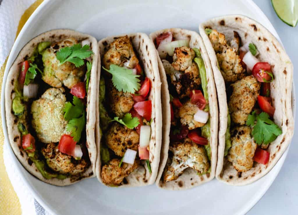 four roasted cauliflower tacos in a white bowl