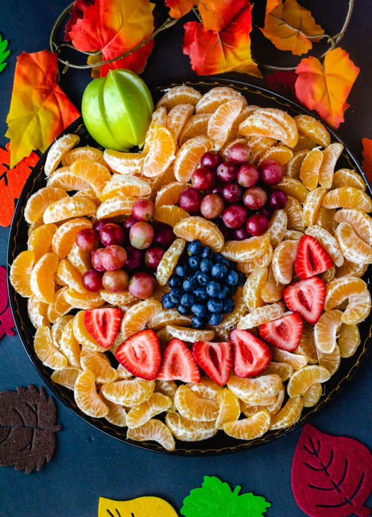 jack-o-lantern fruit tray with oranges, berries, and grapes