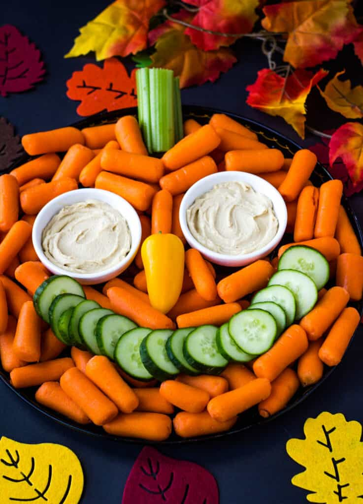 pumpkin face veggie tray surrounds by fall leaves
