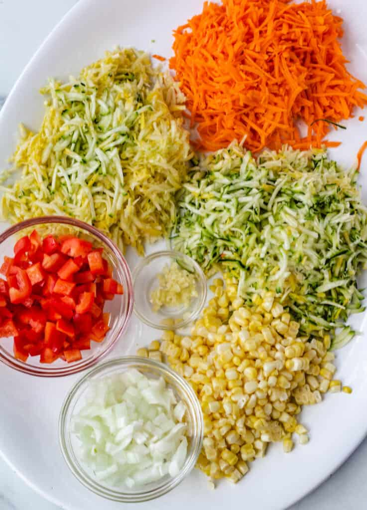 shredded carrot, zucchini, and squash, diced red pepper, and onion on white platter
