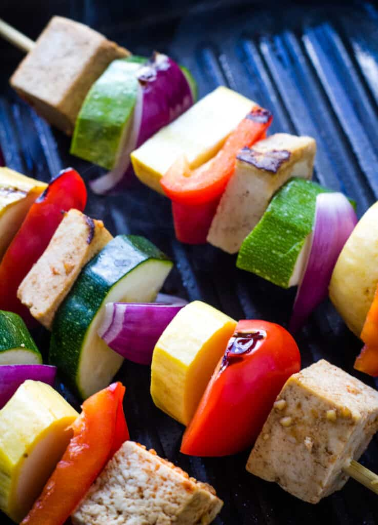 tofu and vegetables on skewers on grill pan
