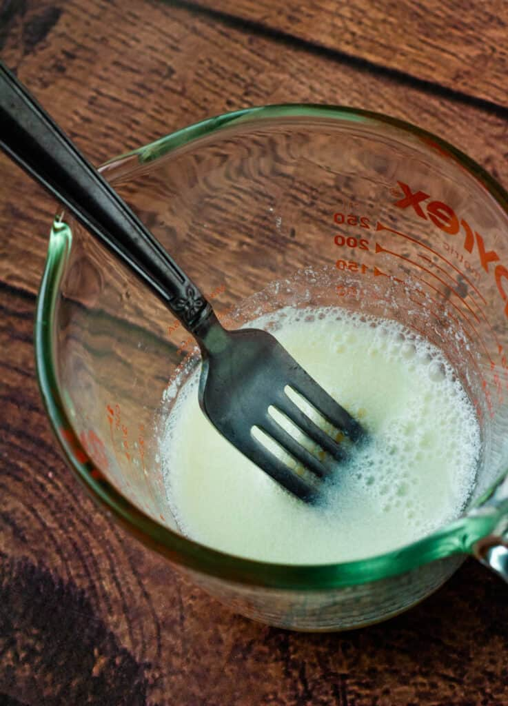 almond milk in measuring cup with fork