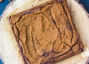 vegan pumpkin brownie square on wood serving plate