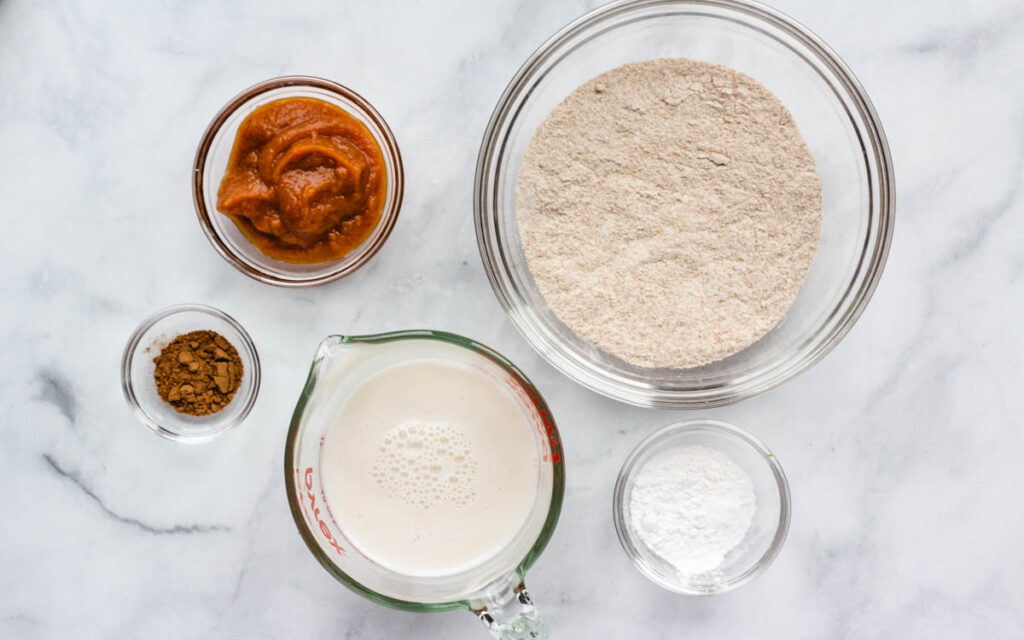 flour, pumpkin puree, milk, baking soda, and spices in glass bowls