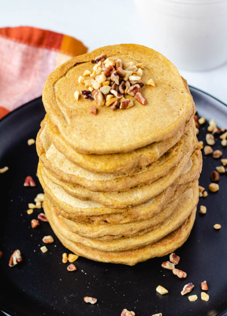 stack of vegan pumpkin pancakes topped with nuts