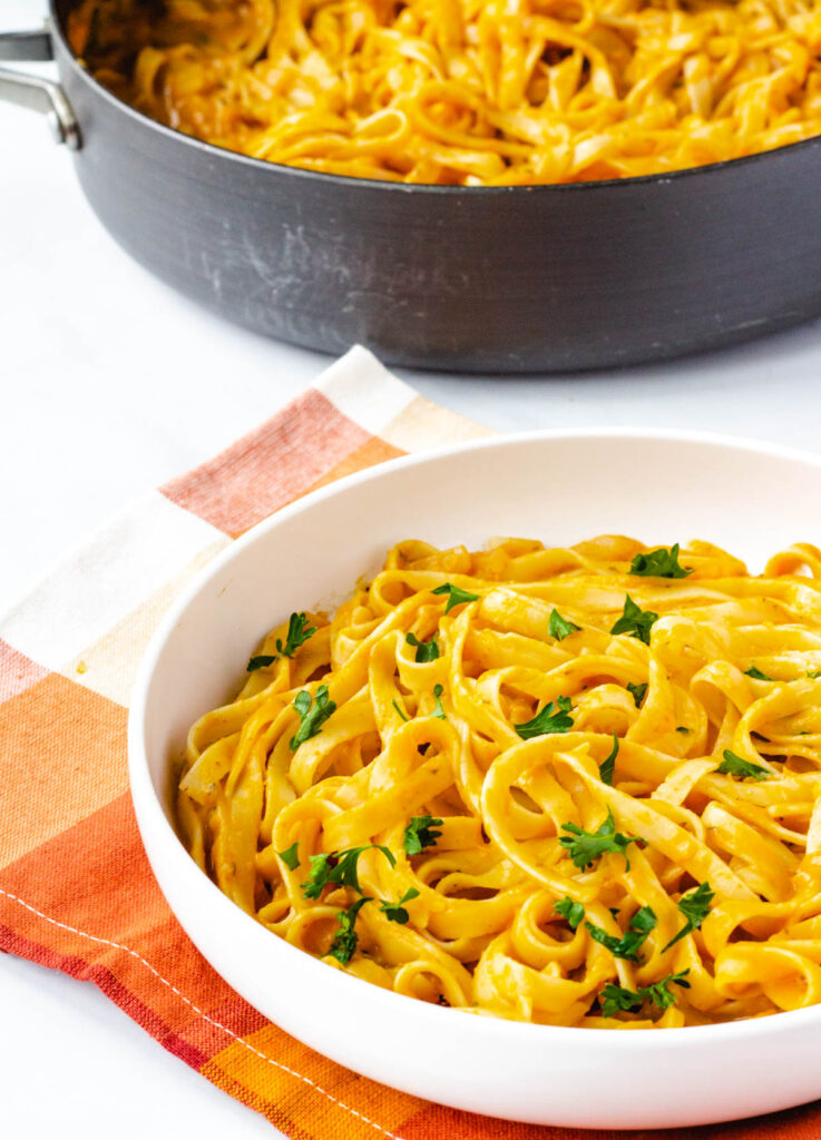 pumpkin pasta in white bowl with pot of pasta in the background