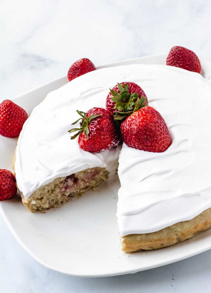 vegan strawberry cake with slice cut out of it