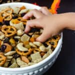 hand reaching for trail mix in white bowl