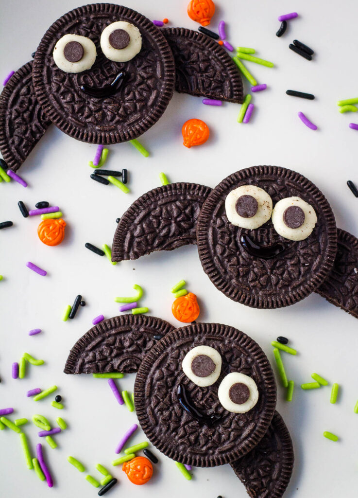 three oreo bats on white plate with sprinkles
