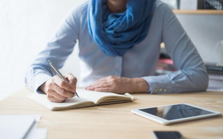 woman writing at desk in notebook