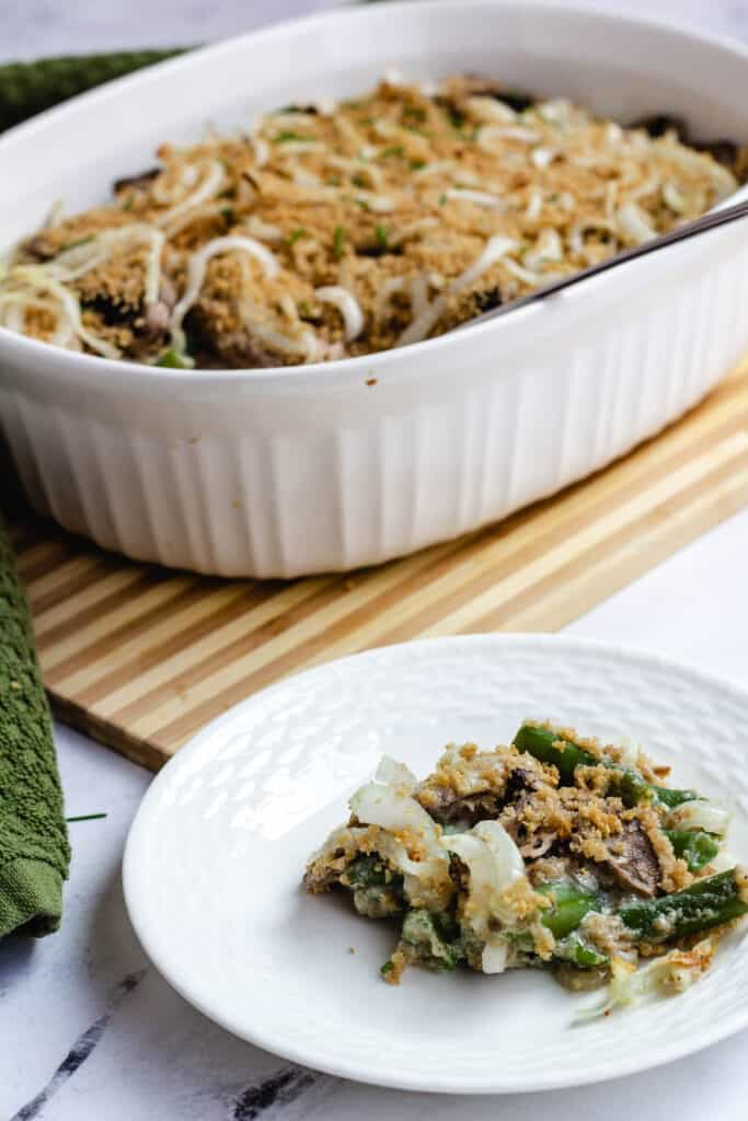 vegan green bean casserole in the background, with a serving on a white plant in the front