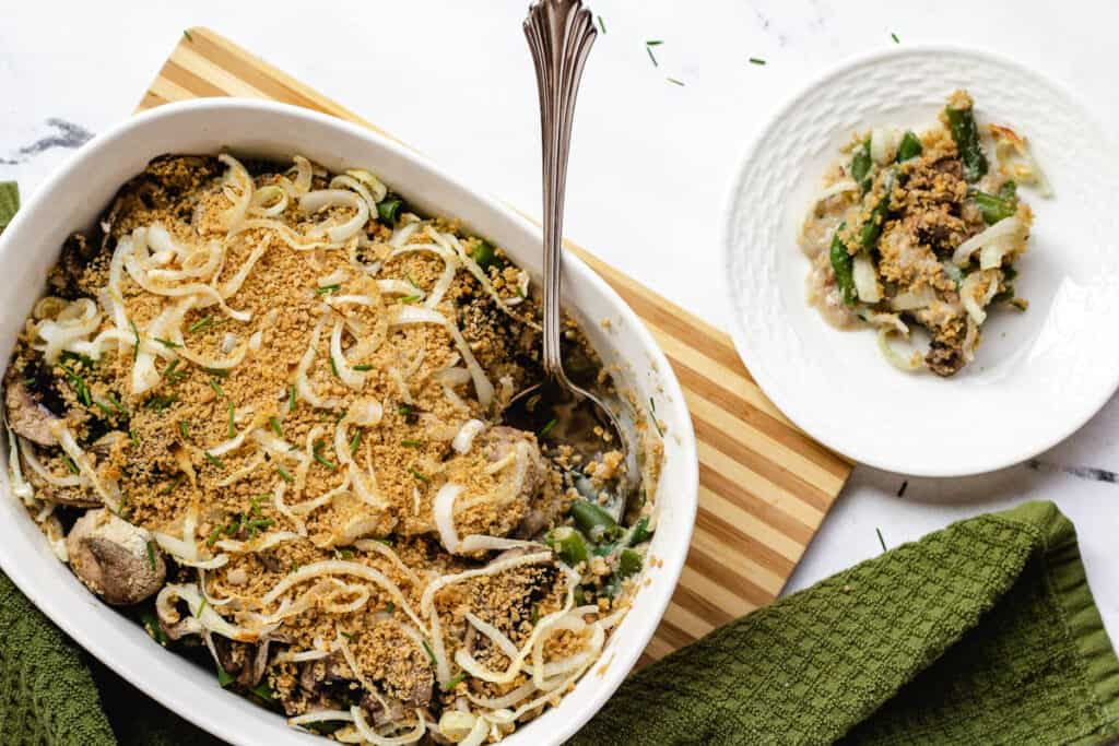 overhead dairy free green bean casserole in casserole dish with single serving on white plate