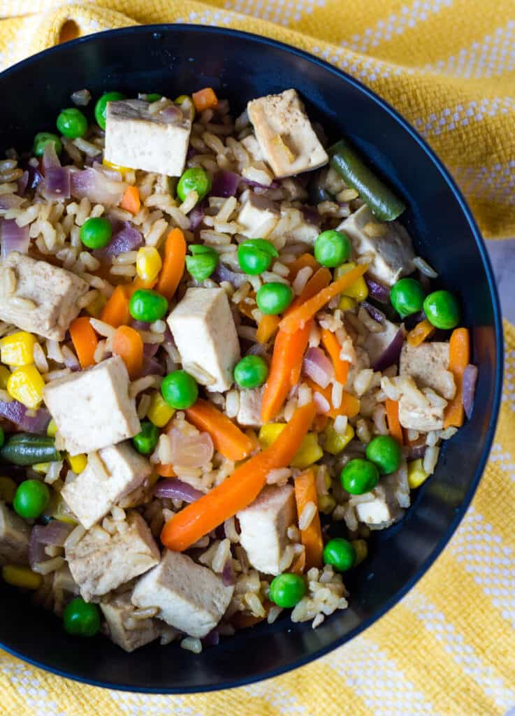 vegan fried rice with tofu in black bowl
