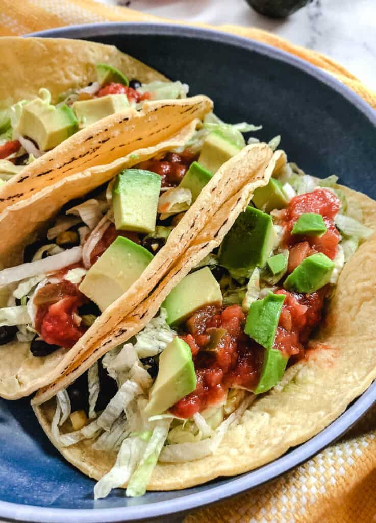 black bean tacos topped with lettuce salsa, and avocado