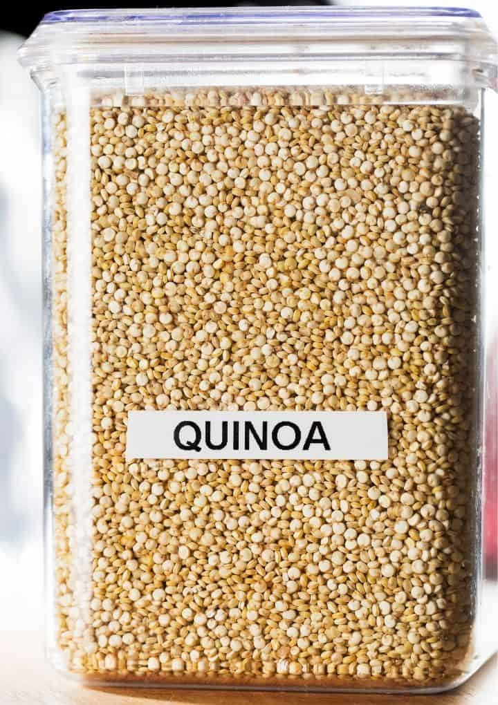 large clear container filled with white quinoa