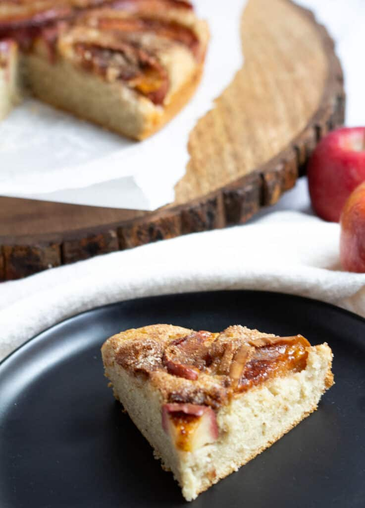 slice of apple cake on plate with apple cake on serving platter in the background