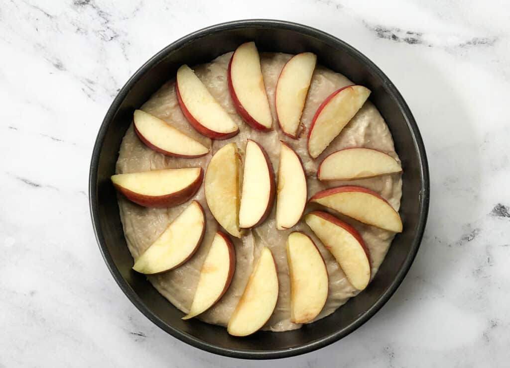 cake batter in pan topped with apple slices