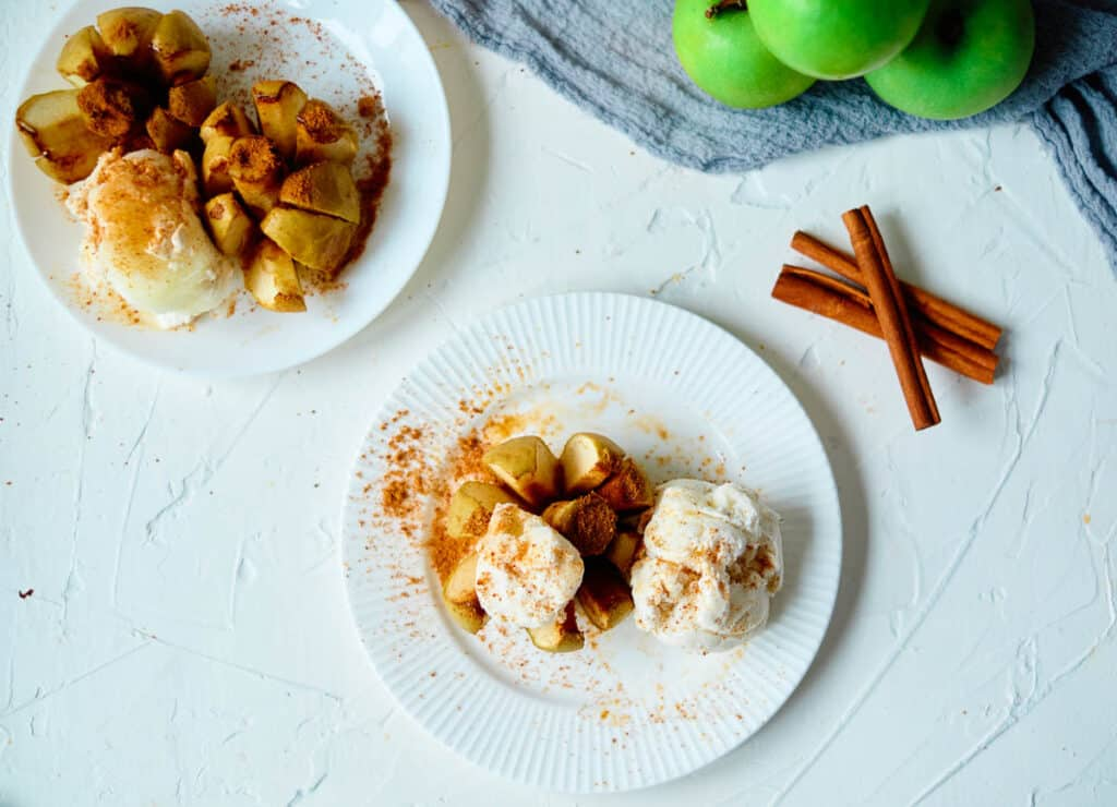overhead of vegan baked apples with cinnamon and coconut milk ice cream with cinnamon sticks and apples