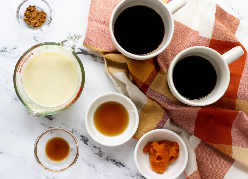 coffee in tow mugs surrounded by milk, maple syrup, spice, and pumpkin puree
