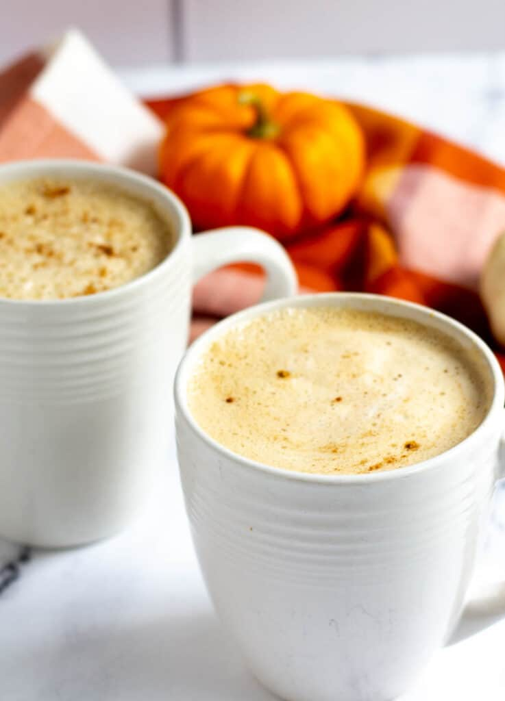 two pumpkin spice lattes in white mugs