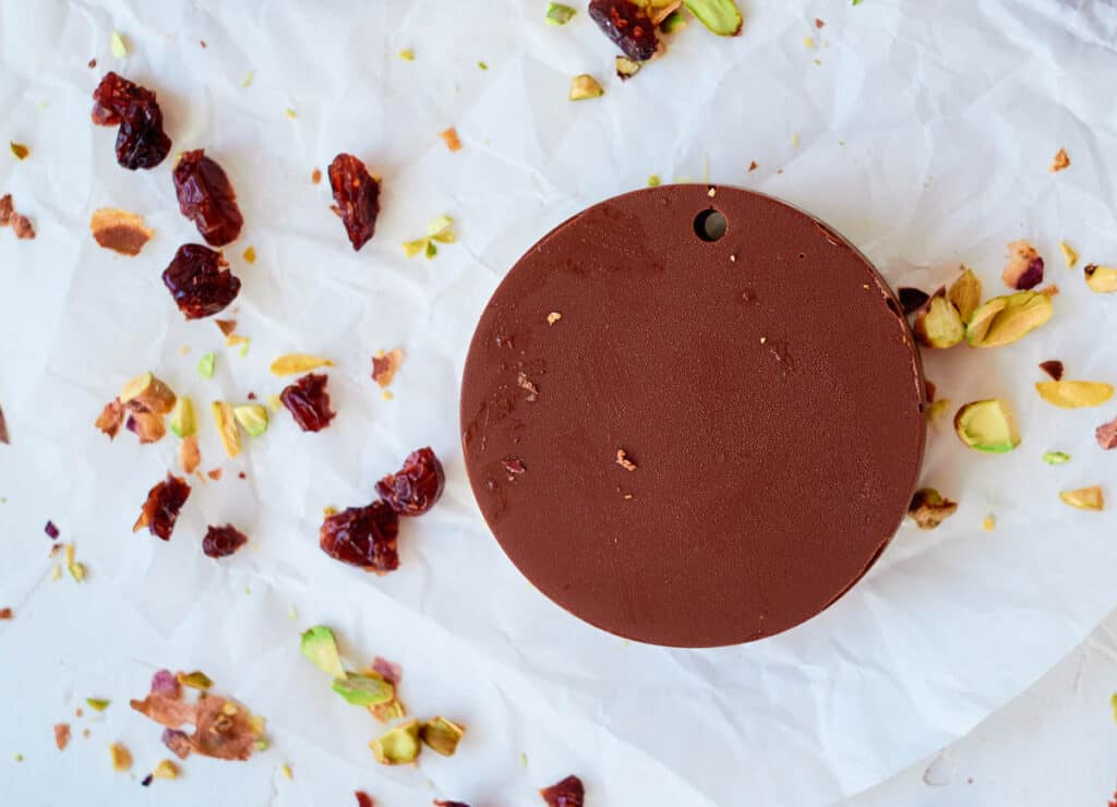 chocolate disks next to chopped pistachios and cranberries