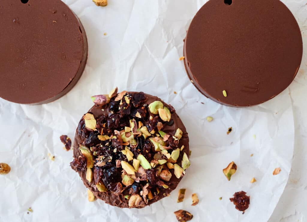 chocolate disk topped with pistachios and cranberries