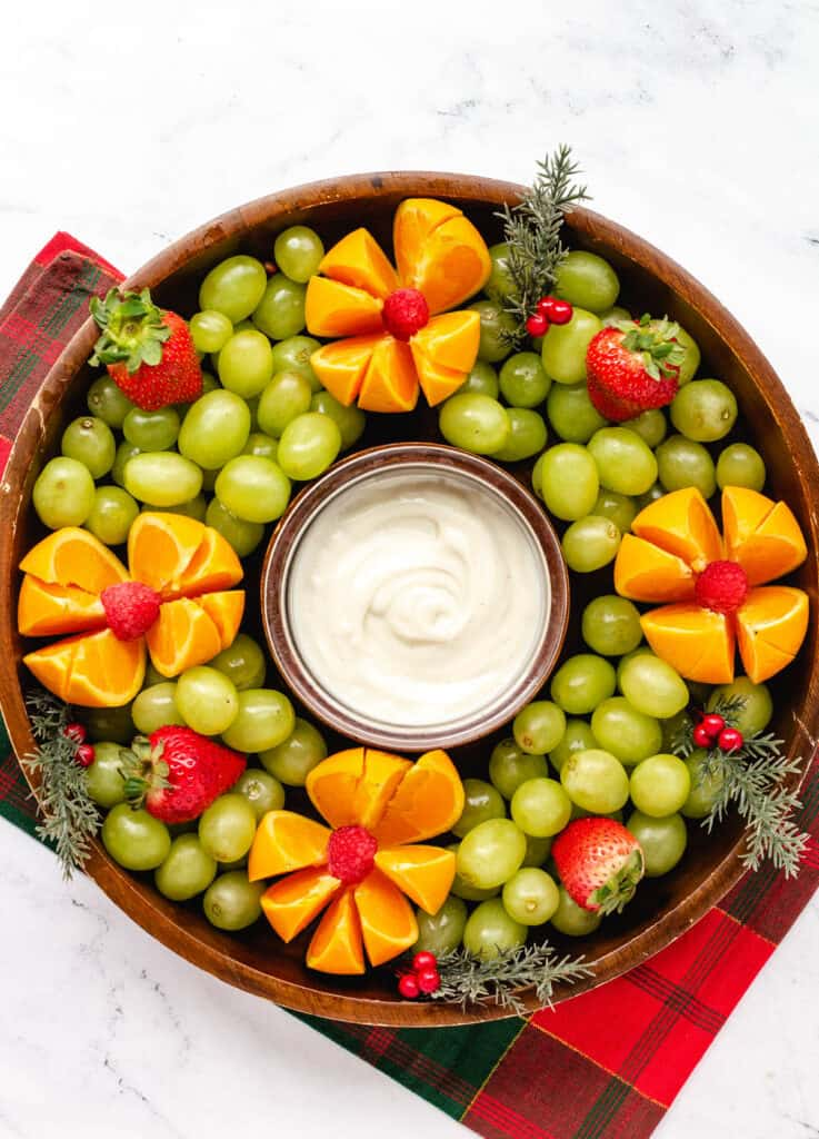 christmas fruit wreath platter made of green grapes, oranges, strawberries, and raspeberries, with a vegan yogurt dip in the center