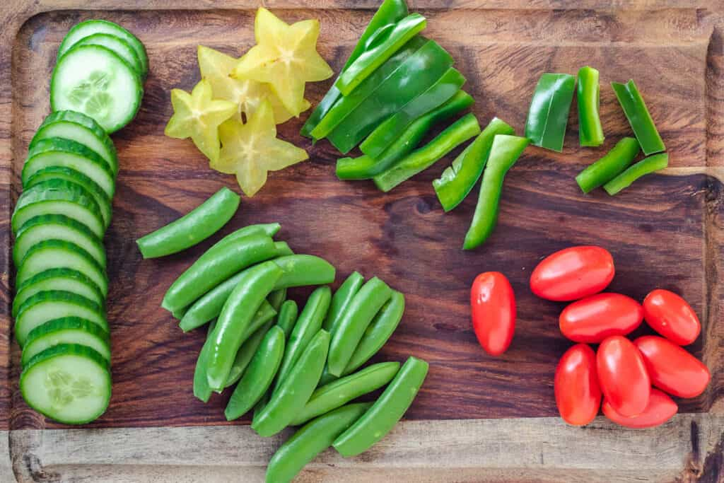 prepared vegetables on cutting board: sliced cucumber, chopped green peppers, chopped starfruit, snap peas, and grape tomatoes