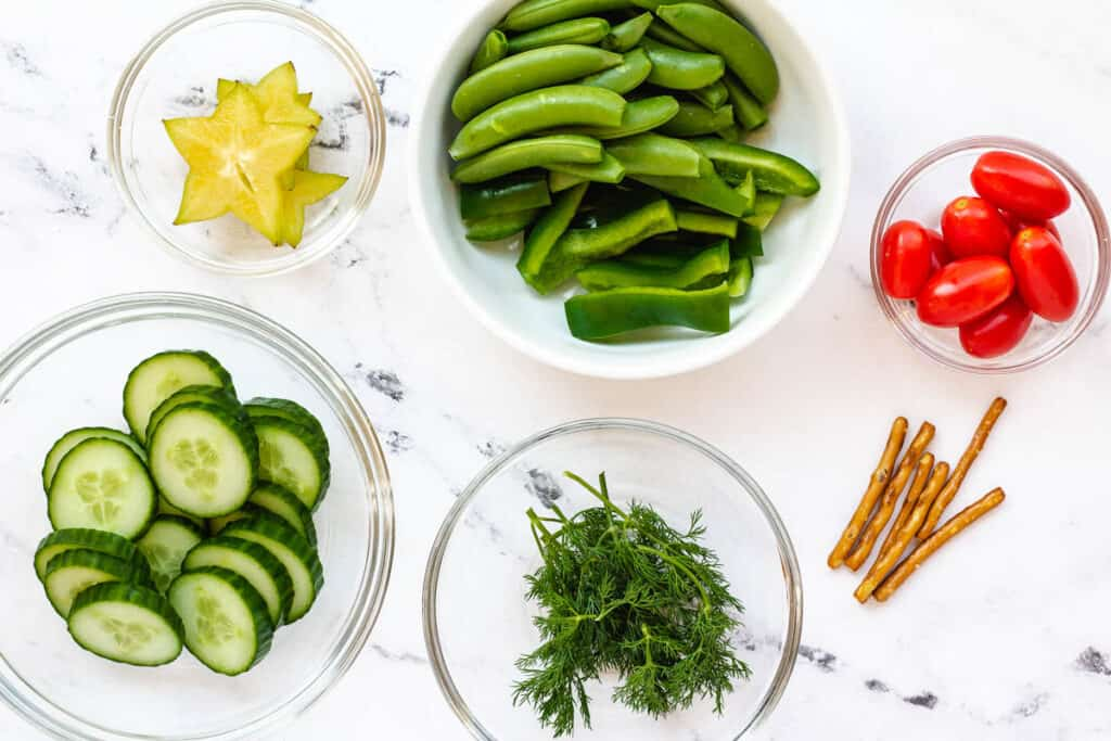 cucumbers, green peppers, snap peas, dill, tomatoes, starfruit, dill and pretzels on counter top