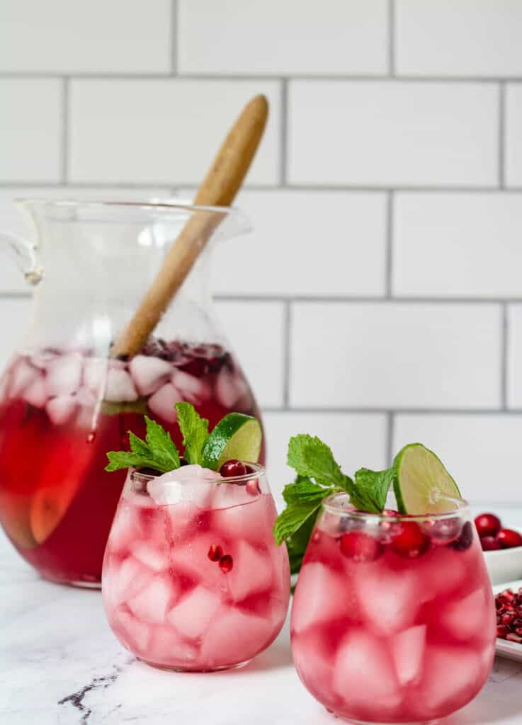 2 cranberry mocktails in stemless wine glasses with pitcher in the background