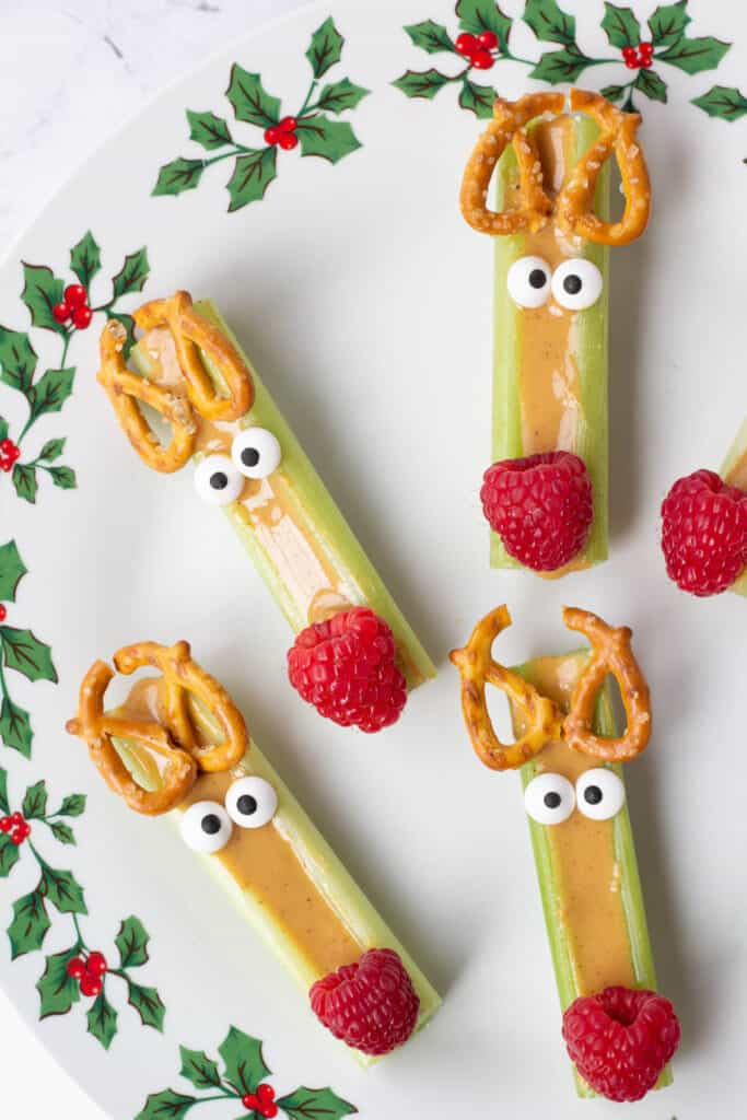 reindeer celery snacks with peanut butter, pretzels, candy eyes, and a raspberry nose
