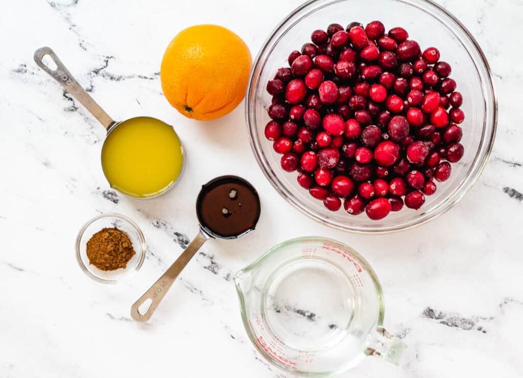 cranberries, orange, orange juice, cinnamon, water and maple syrup on counter top