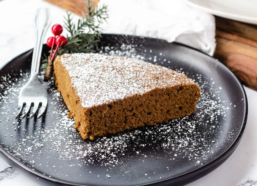 slice of cake dusted with powdered sugar on black plate