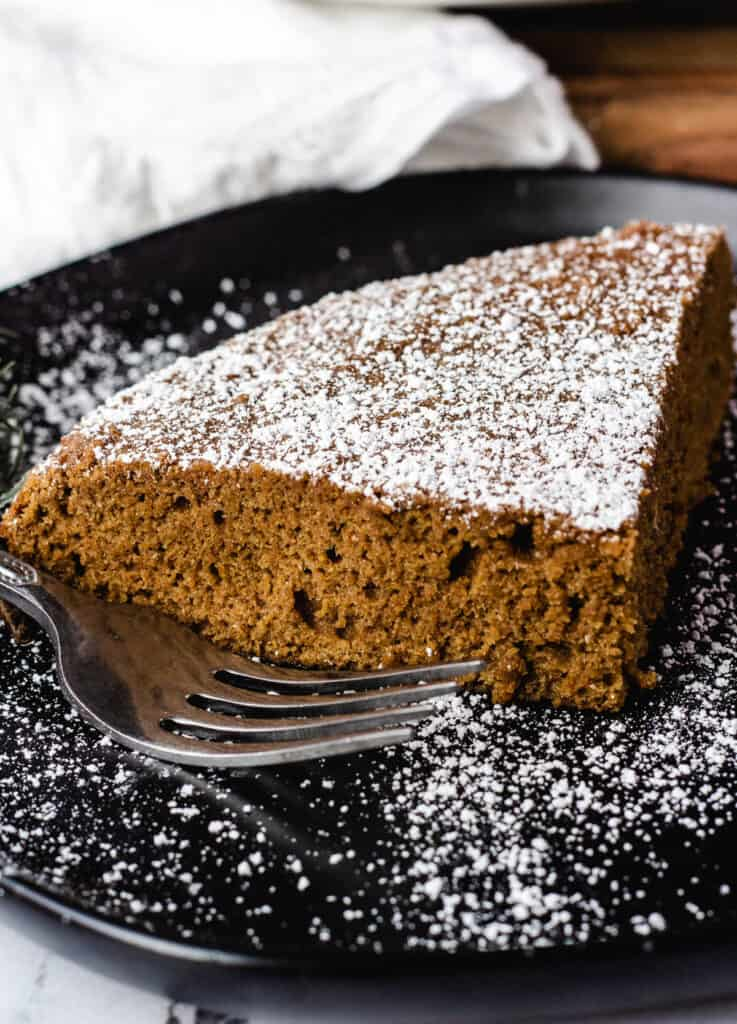 vegan ginger cake dusted with powdered sugar on black plate