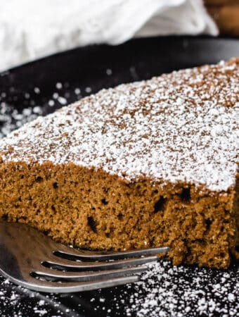 vegan ginger cake slice dusted with powdered sugar on black plate